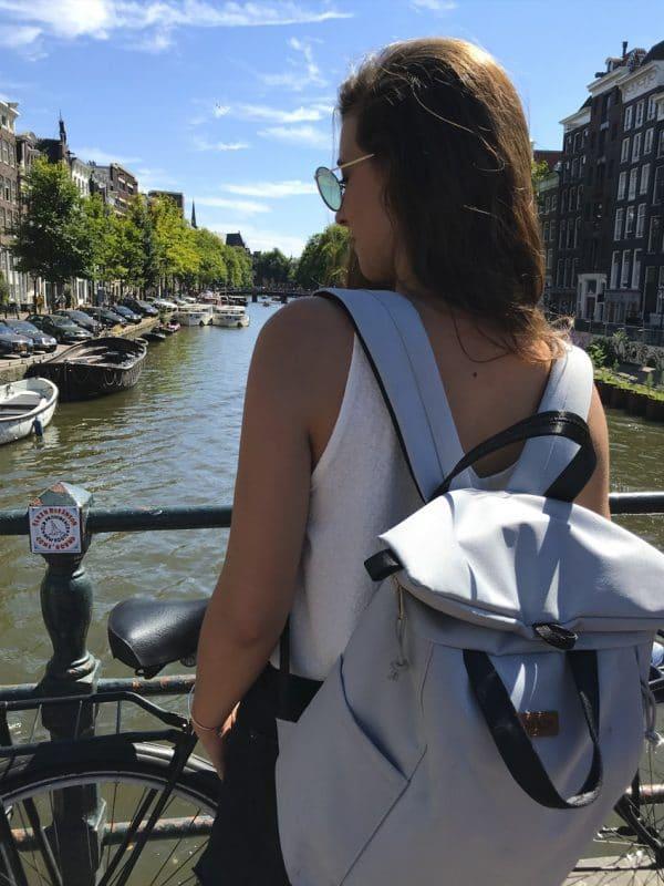 Junge Frau mit Rucksack vor einer Gracht